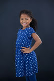 Portrait of cheerful girl with hand on hip. Standing against black background Stock Photo