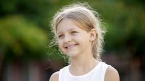 Portrait of cheerful girl with long hair standing outdoors. Closeup portrait of happy girl in elementary school age outdoors stock footage