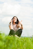 Portrait of cheerful girl thumbup and relaxing on meadow. While listening music on headphones Royalty Free Stock Photos