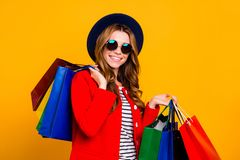Portrait of cheerful glad charming elegant adorable curly-haired. Lady in round  eyeglasses eyewear holding many colorful bags wearing fall season outfit royalty free stock photo