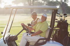 Portrait of cheerful golfer friends sitting in golf buggy Stock Image