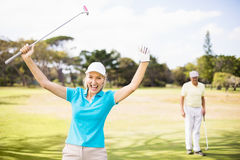 Portrait of cheerful golfer woman with arms raised. Portrait of cheerful golfer women with arms raised while standing on field Stock Photos