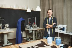 Portrait of cheerful good-looking male clothes designer with dark hair in fashionable outfit standing in workshop. Posing for article about his brand. Artist Stock Photography
