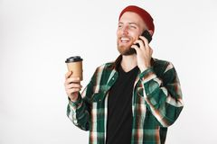 Portrait of cheerful guy wearing plaid shirt holding paper cup with coffee and using mobile phone, while standing isolated over. Portrait of cheerful guy wearing stock image