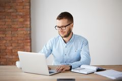 Portrait of cheerful handsome unshaven male company manager in glasses and casual clothes sitting at table in office. Smiling gently, looking at laptop stock photo