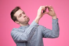 Portrait of a cheerful handsome young man taking selfie on his phone. Standing over pink background stock photography