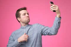 Portrait of a cheerful handsome young man taking selfie on his phone. Standing over pink background royalty free stock image