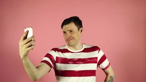 Portrait of a cheerful handsome young man taking selfie on his phone standing over pink background stock video