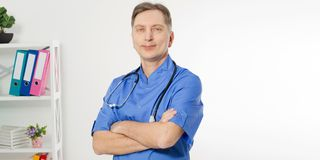 Portrait of cheerful happy male doctor in hospital with crossed hands. Surgeon with stethoscope on white background. Medical royalty free stock images