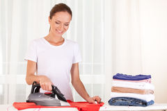 Portrait of cheerful housewife ironing clothes. Royalty Free Stock Image