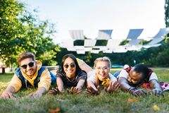 portrait of cheerful interracial young friends lying on green grass in park stock photos