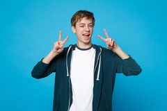 Portrait of cheerful joyful young man in casual clothes blinking and showing victory sign isolated on blue wall. Background in studio. People sincere emotions royalty free stock photography