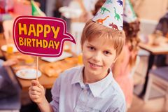 Portrait of cheerful kid that holding namecard. Real celebration. Handsome blonde boy expressing positivity while looking straight at camera stock photos