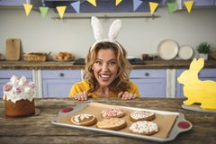 Merry female showing her glee. Portrait of cheerful lady in funny bunny headband sitting at kitchen table with easter cake, cookies and yellow rabbit statuette royalty free stock photos