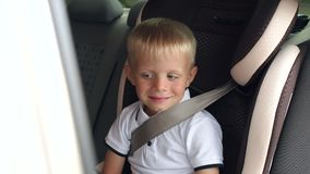 Portrait of cheerful laughing boy in a children`s car seat during a summer trip. Portrait of a cheerful laughing boy in a children`s car seat during a summer stock video footage