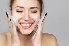 Portrait of cheerful laughing girl applying foam for washing on her face. Lovely woman redhead with attractive appearance. Skin. Portrait of cheerful laughing royalty free stock photo
