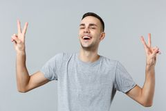 Portrait of cheerful laughing young man in casual clothes looking camera showing victory sign isolated on grey wall stock photography