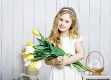 Portrait of cheerful little blonde girl with tulips bouquet on w Stock Photos