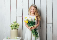 Portrait of cheerful little blonde girl with tulips bouquet on white wood background Stock Photography