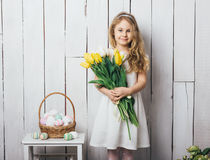 Portrait of cheerful little blonde girl with tulips bouquet on white wood background Stock Photo