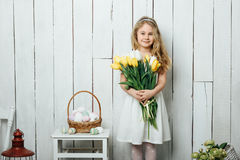 Portrait of cheerful little blonde girl with tulips bouquet on white wood background Stock Image