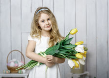 Portrait of cheerful little blonde girl with tulips bouquet on white wood background Royalty Free Stock Photography