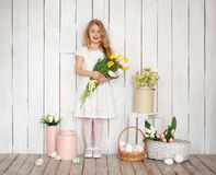 Portrait of cheerful little blonde girl with tulips bouquet on white wood background Stock Photos