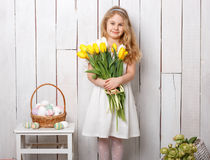 Portrait of cheerful little blonde girl with tulips bouquet on white wood background Royalty Free Stock Images
