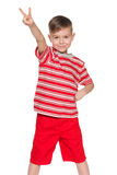 Cheerful little boy in red shows victory sign Stock Image