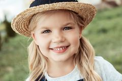 Portrait of cheerful little caucasian girl. In straw hat looking at camera Stock Images