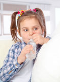 Portrait of a cheerful little girl drinking water from a bottle Stock Photography