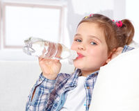 Portrait of a cheerful little girl drinking water from a bottle Royalty Free Stock Image