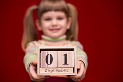 Portrait of cheerful little girl isolated on red hold wooden calendar set on first september stock photos