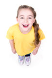 Portrait of cheerful little girl looking up. Portrait of cheerful little girl looking up in yellow t-shirt. Top view. Isolated on white background Royalty Free Stock Images