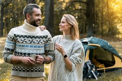 Joyful man and woman enjoying hot beverage in the nature. Portrait of cheerful loving couple relaxing in the forest together. They are standing and drinking tea Stock Photography