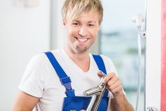 Portrait of a cheerful maintenance worker holding a faucet in a stock photography