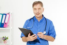 Portrait of cheerful male doctor in hospital takes notes. Surgeon with stethoscope on white background. Medical insurance Copy stock photo