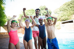 Portrait of cheerful male instructor with little swimmers. At poolside Stock Photos