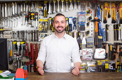 Portrait of cheerful man at the cash desk working in tool-ware s. Portrait of young cheerful european man at the cash desk working in tool-ware shop Stock Image