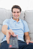 Portrait of a cheerful man changing channel Royalty Free Stock Photo