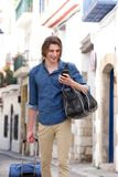 Cheerful man in city street with smart phone and luggage Royalty Free Stock Photography