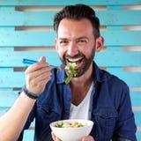 Portrait of cheerful man eating salad stock photo