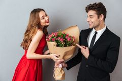 Portrait of a cheerful man giving his girlfriend flower bouquet Royalty Free Stock Photos