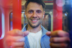 Portrait of cheerful man listening music. In train Royalty Free Stock Image