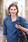 Cheerful man with long hair holding smart phone and bag. Portrait of cheerful man with long hair holding smart phone and bag Royalty Free Stock Image