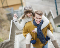 Portrait of cheerful man piggybacking woman on stairway Royalty Free Stock Images
