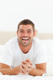 Portrait of a cheerful man relaxing in his bedroom Stock Photos