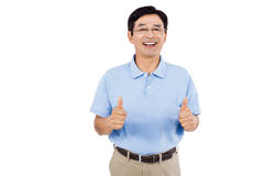 Portrait of cheerful man showing thumbs up while standing Stock Photos