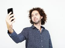 Portrait of a cheerful man taking selfie over white background. Tehnology, emotion and people concept: Portrait of a cheerful man taking selfie over white royalty free stock images