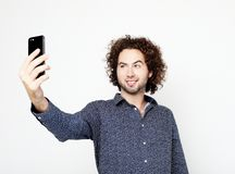 Portrait of a cheerful man taking selfie over white background. Tehnology, emotion and people concept: Portrait of a cheerful man taking selfie over white stock photography